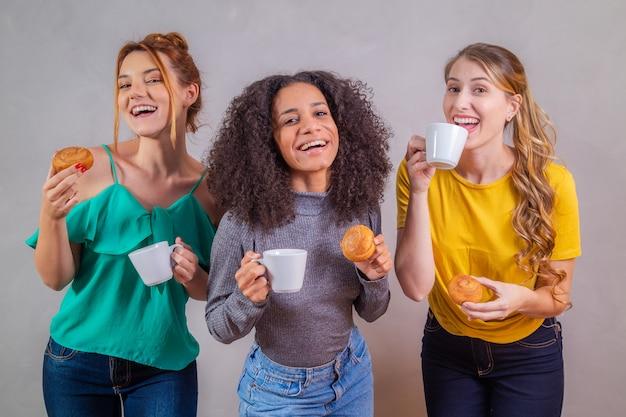 Vrienden bij afternoon tea donuts eten en koffie drinken met melk