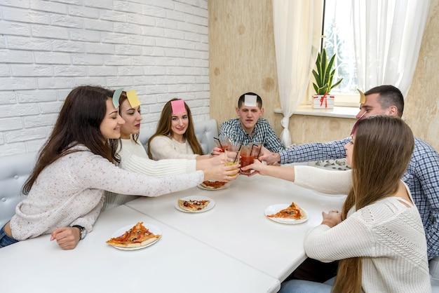 Vrienden bij cafe genieten van weekend, pizza eten en kletsen