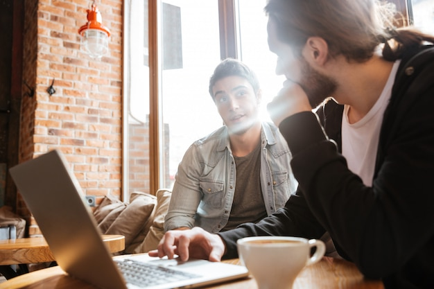 Vrienden bij de tafel met laptop