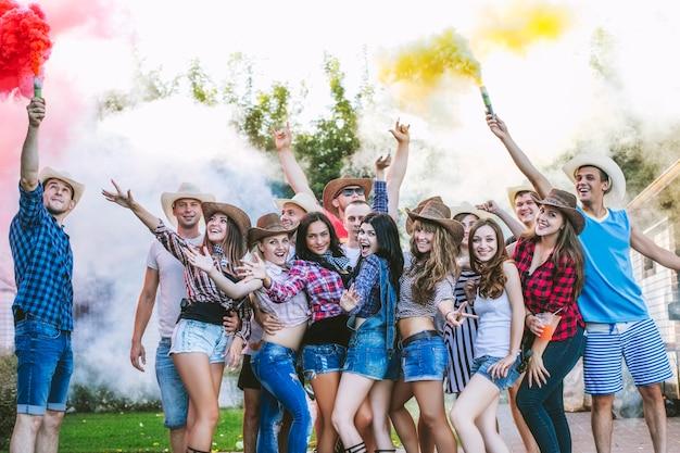 Vrienden blij op het feest grappig jong samen met een glimlach en crackers met gekleurde rook