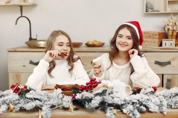 Vrienden brachten tijd thuis door. twee meisjes drinken thee. vrouw in de hoed van een kerstman.