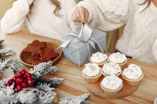 Vrienden brachten tijd thuis door. twee meisjes met kerstcadeau. vrouw in de hoed van een kerstman.