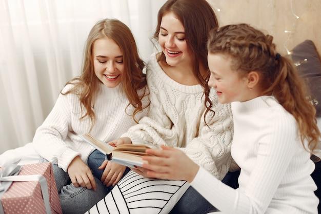 Vrienden brachten tijd thuis door. vrouwen met cadeau. zusters met een boek.