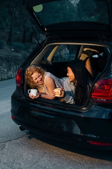 Vrienden communiceren liggend in de open kofferbak