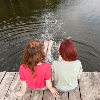 Vrienden die aan de kade blijven en met hun voeten water spetteren +