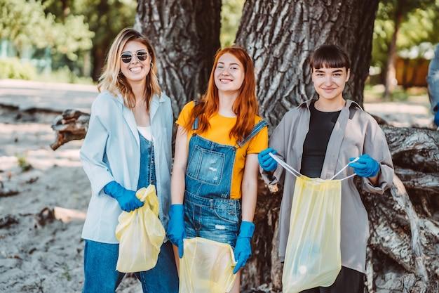 Vrienden die afval uit het park oppakken. ze verzamelen het afval in een vuilniszak