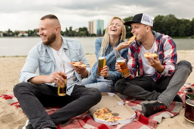 Vrienden die bier drinken en pizza eten