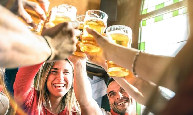 Vrienden die bier drinken en roosteren in het restaurant van de brouwerijbar