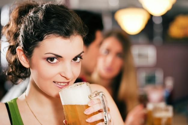 Vrienden die bier in bar drinken