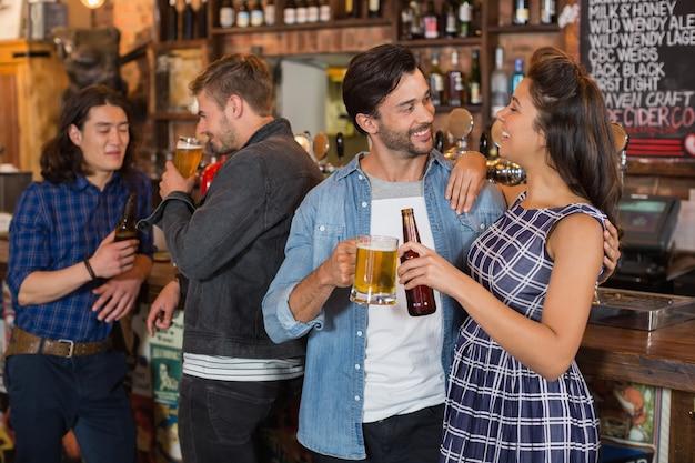 Vrienden die bierglas en fles houden door teller in pub