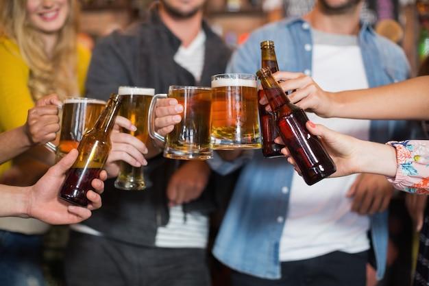 Vrienden die bierglazen en flessen roosteren in de pub