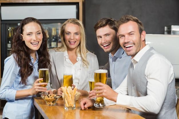Vrienden die bij camera met in hand bieren glimlachen