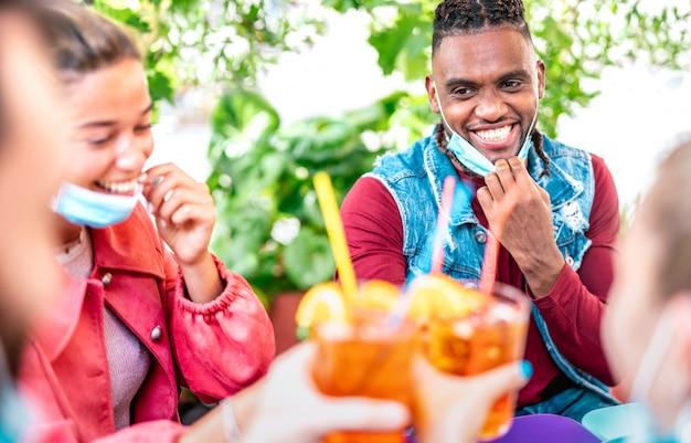 Vrienden die bij cocktailbar drinken met gezichtsmaskers