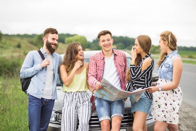 Vrienden die bij de kaart van de mensenholding lachen