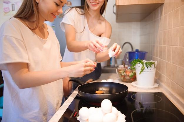 Vrienden die brekfast prepearing en samen maaltijd in keuken hebben.
