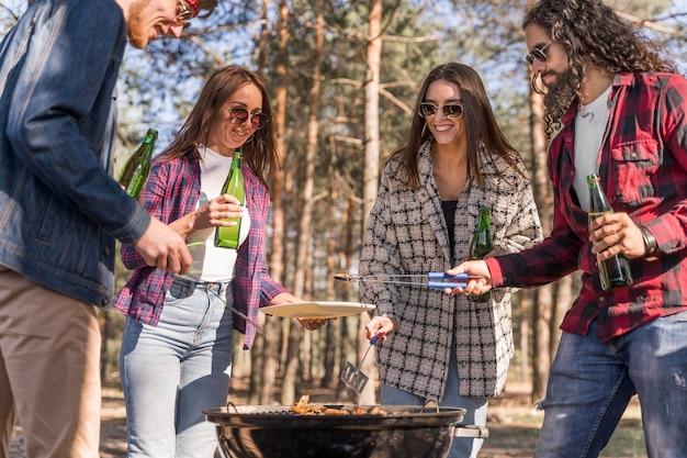 Vrienden die buiten bier hebben en een barbecue maken