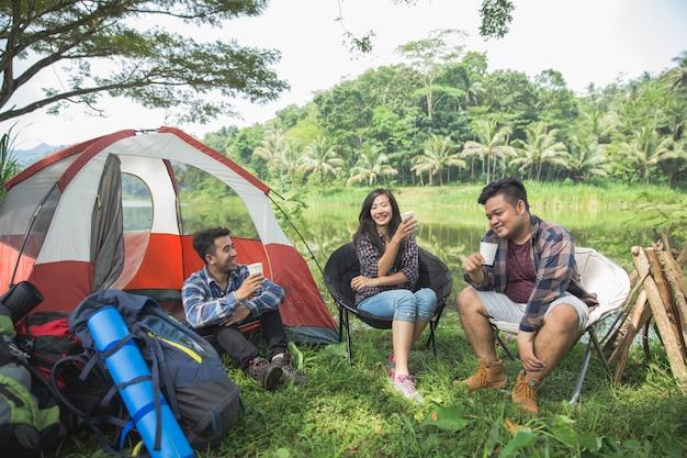 Vrienden die buitententen bij het kamperen ontspannen