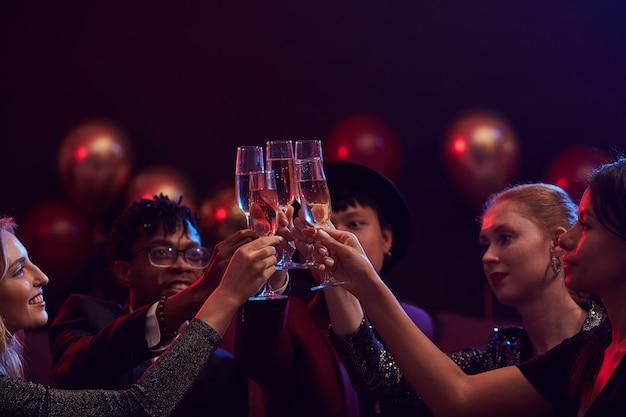 Vrienden die champagneglazen in nachtclub opheffen