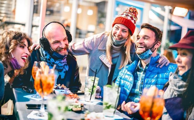Vrienden die cocktail drinken in openluchtbarrestaurant