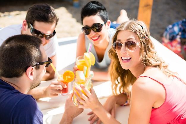 Vrienden die cocktails in strandbar drinken