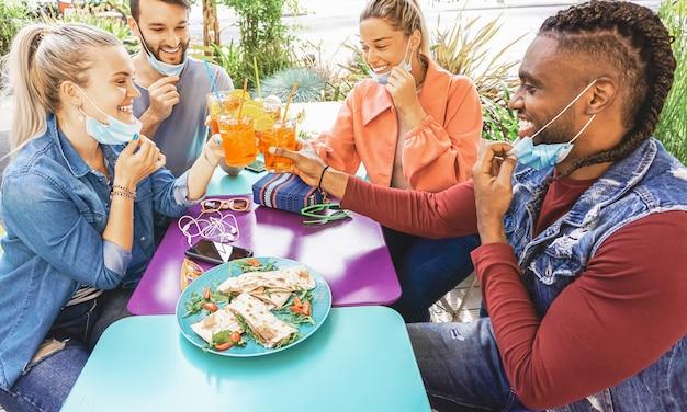 Vrienden die coktail drinken en snacktapas eten in een restaurantbar buiten in de zomerdagen met gezichtsmasker op om te worden beschermd tegen coronavirus