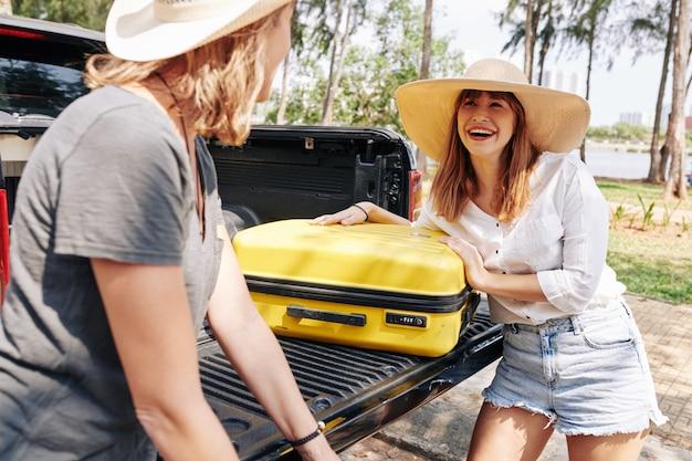 Vrienden die de kofferbak van de auto uitladen