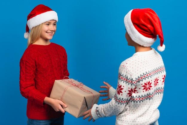Vrienden die de studioschot van de kerstmisgift houden