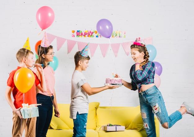 Vrienden die de verjaardag van het meisje met cake vieren