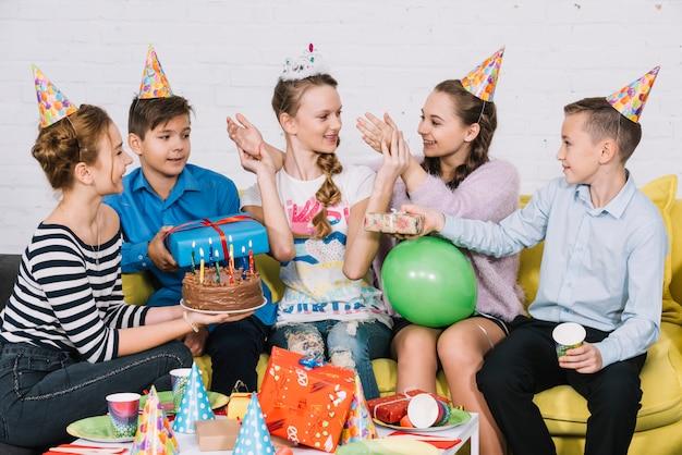 Vrienden die de verjaardagstaart en de giften geven aan hun vriend in het feest