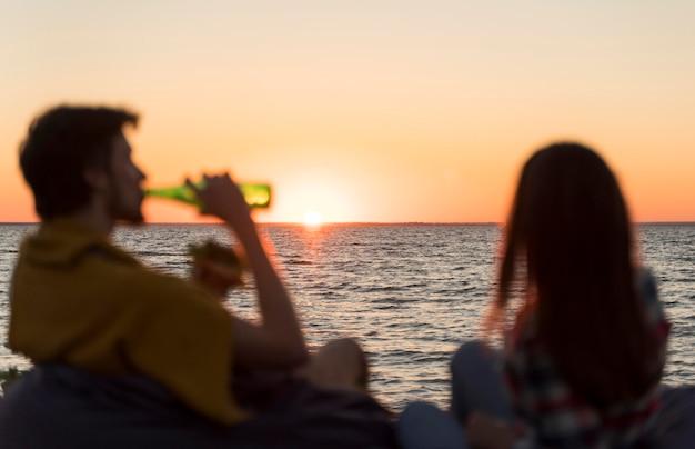 Vrienden die de zonsondergang bewonderen terwijl ze een biertje drinken