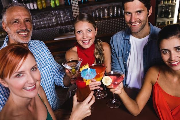 Vrienden die drankglazen in nachtclub roosteren