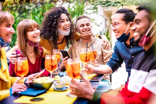 Vrienden die drankjes roosteren bij cocktailbar met gezichtsmasker
