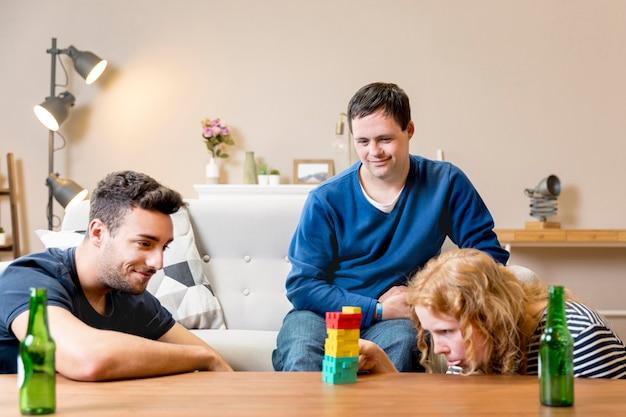 Vrienden die een biertje hebben en spelen thuis spelen