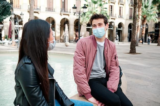 Vrienden die een gezichtsmasker dragen en buiten praten