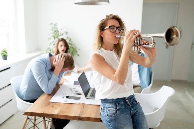 Vrienden die een grap uithalen met hun collega op kantoor. overwerkt business team