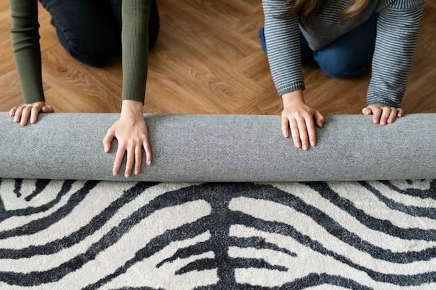 Vrienden die een tapijt rollen