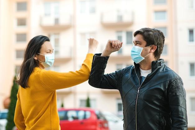 Vrienden die ellebogen in openlucht schudden. mensen houden sociale afstand om te voorkomen dat het virus zich verspreidt. jong koppel groet met ellebogen.