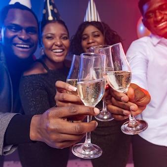 Vrienden die feestmutsen dragen en met champagne roosteren