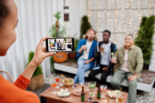 Vrienden die foto's maken op een buitenfeest