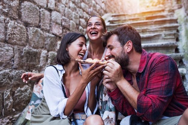 Vrienden die heerlijke pizza eten op straat