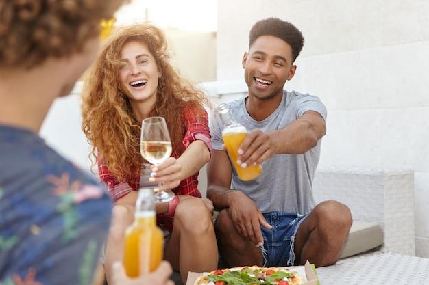 Vrienden die hun glazen rammelen met wijn en bier