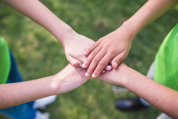 Vrienden die hun handen samen stapelen