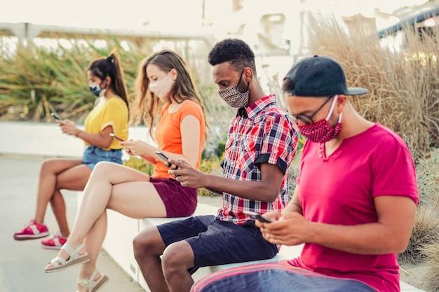 Vrienden die hun smartphones gebruiken in covid 19 keer beschermd met gezichtsmasker