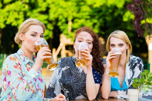 Vrienden die in biertuinrestaurant drinken