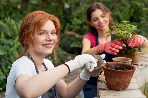 Vrienden die in een kas voor hun planten zorgen
