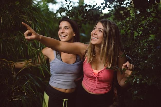 Vrienden die in het bos lopen en op aard wijzen