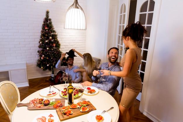 Vrienden die kerstmis of nieuwjaarvooravond thuis vieren