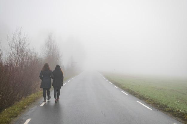 Vrienden die langs een weg lopen die naar de mist leidt