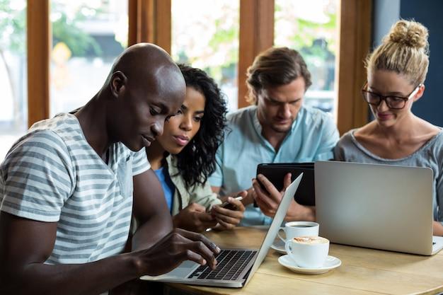 Vrienden die laptop, mobiele telefoon en digitale tablet gebruiken terwijl het hebben van koffie