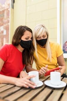 Vrienden die maskers dragen en samen genieten van een kopje koffie